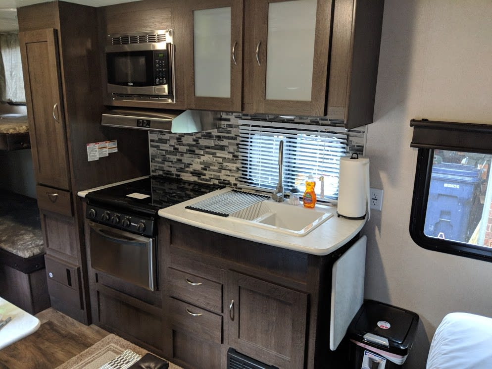 Kitchen including microwave, 3 burner stove, double sink and oven!. Forest River Wildwood X-Lite 2019