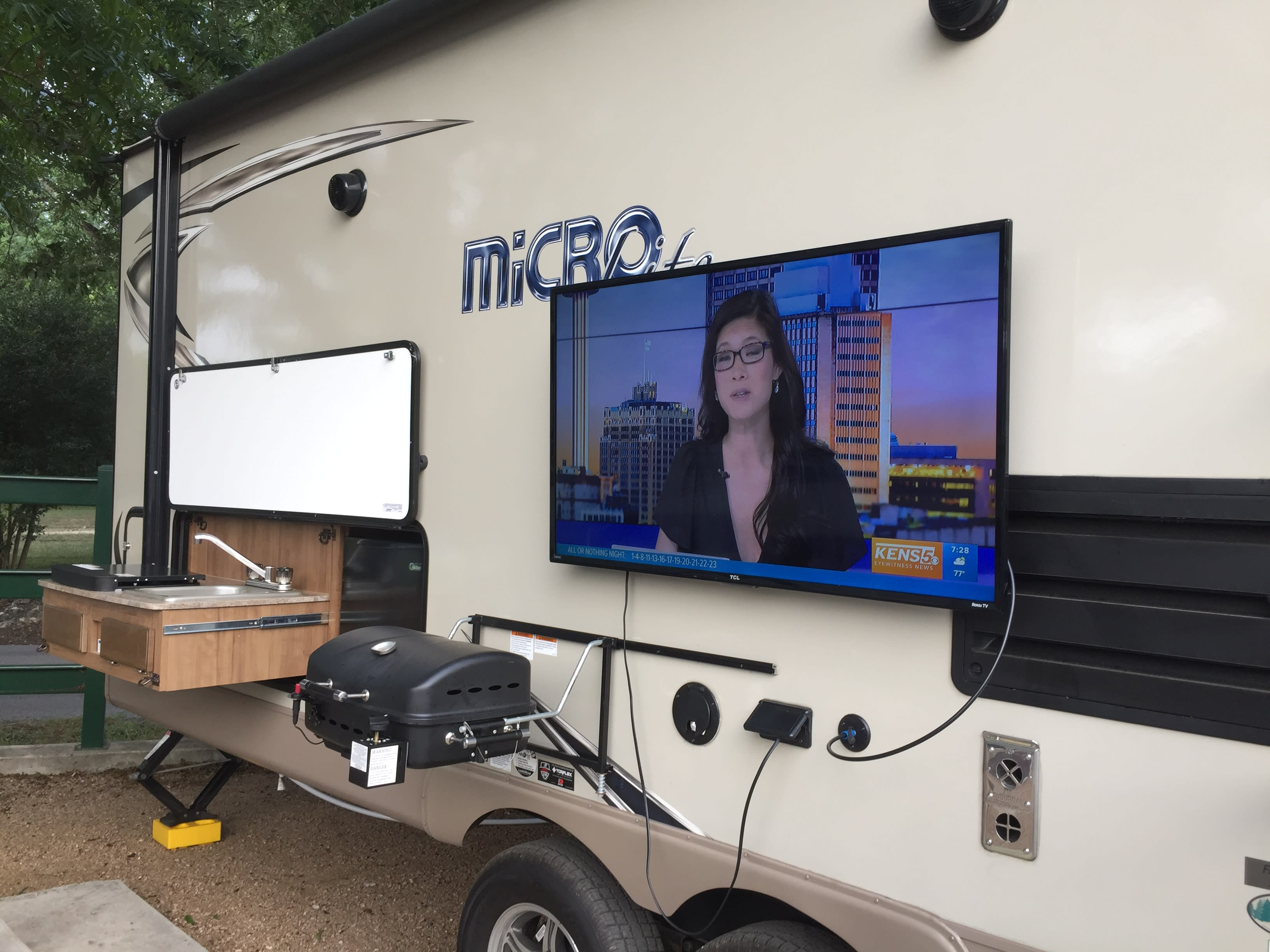 Outside kitchen with gas grill, refrigerator and 2 burner stove and we provide another tv. Forest River Flagstaff Micro Lite 2018