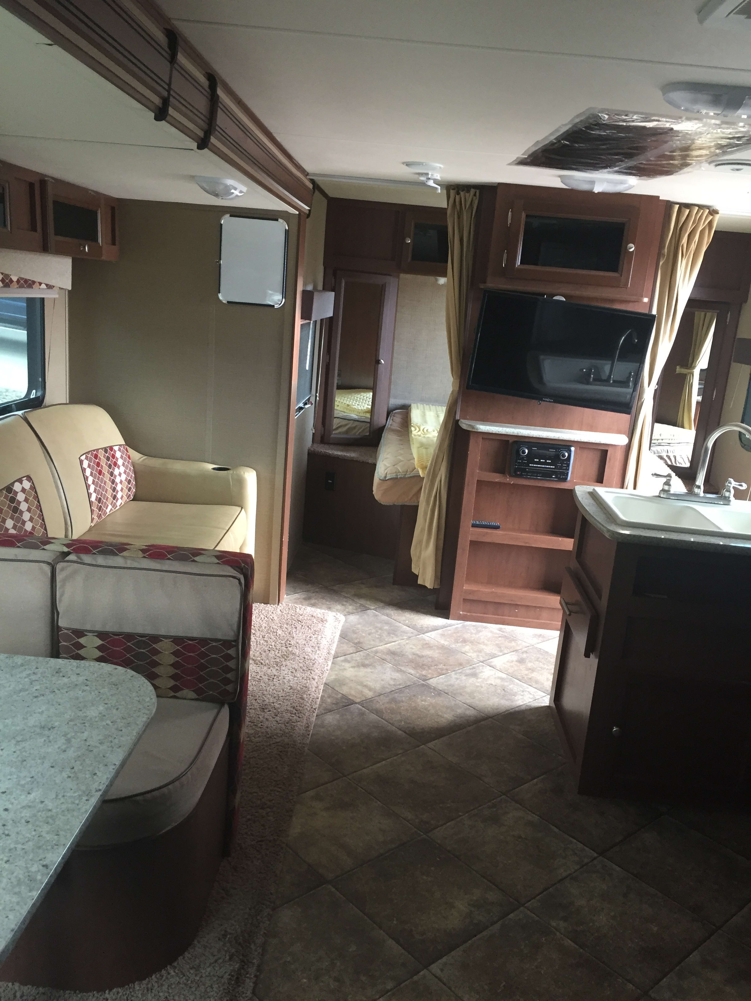 Looking at queen bed, TV, couch and sink. Dutchmen Kodiak 2015