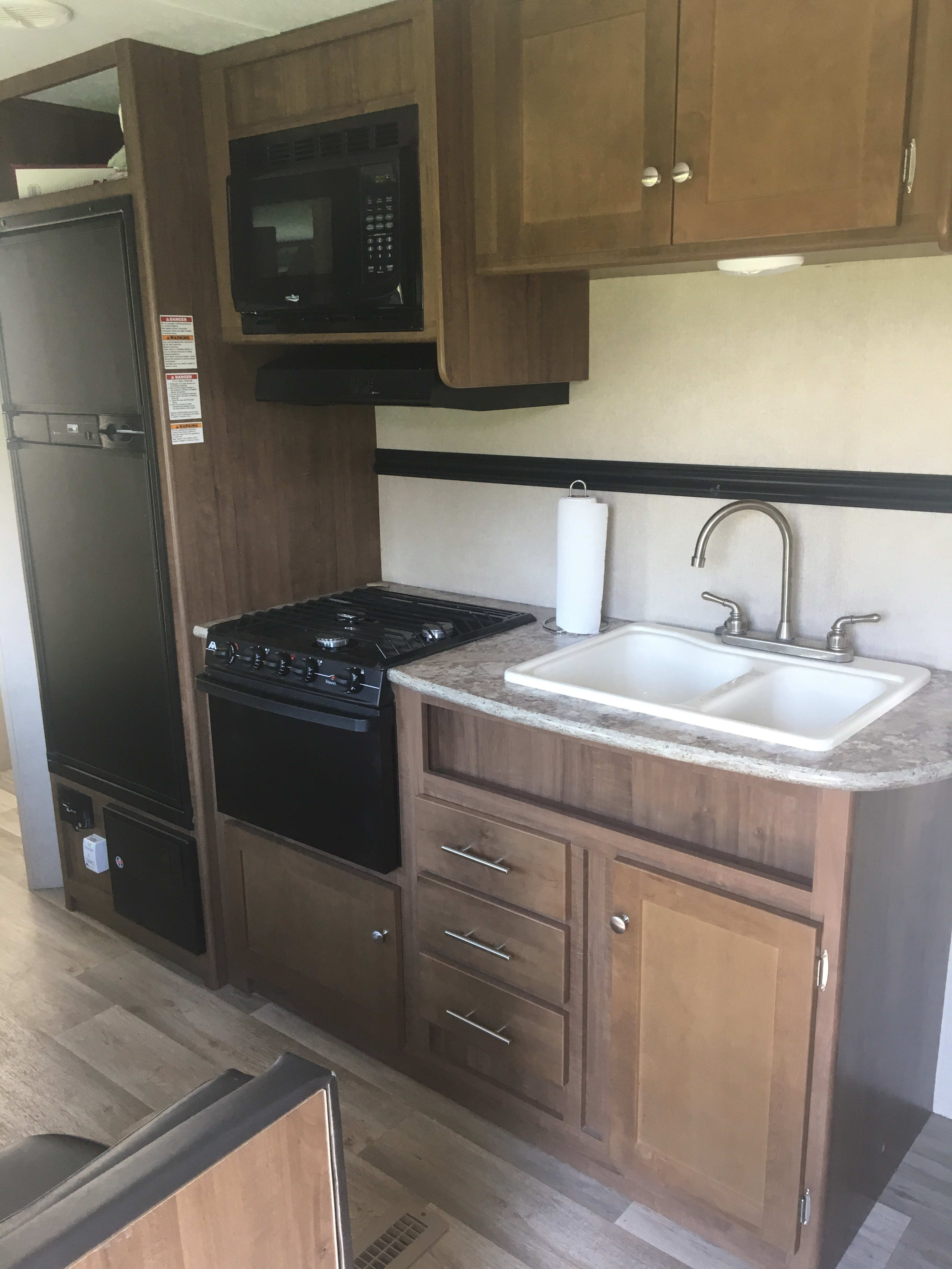 With a freezer, fridge, three burner stove, oven, microwave and two basin sink, this kitchen brings all of the comforts of home to wherever your adventure may take you! . Dutchmen Aspen Trail 2016