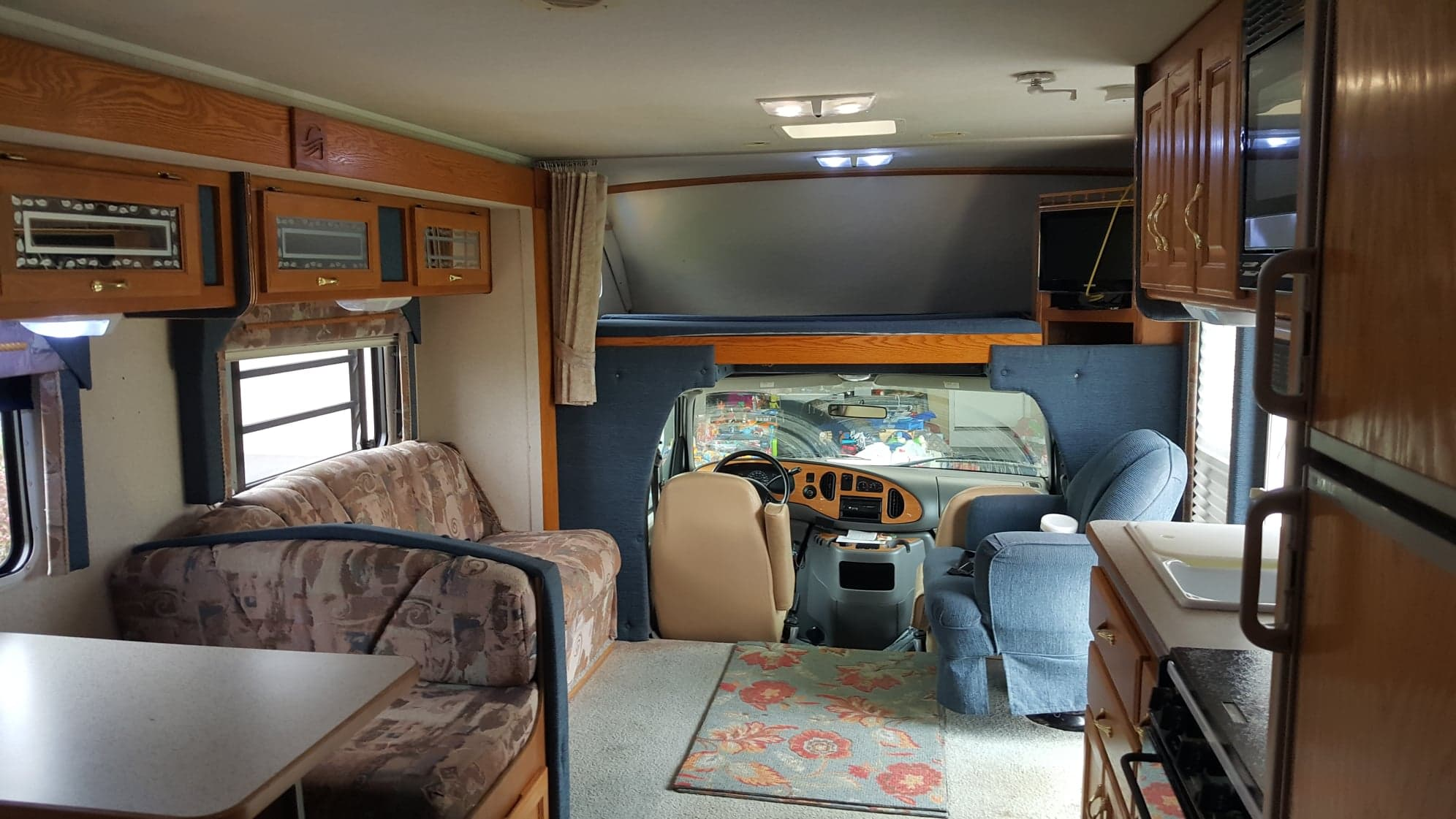 Inside of RV.  The couch and dinette folds down.  Also, sleeping area up top.  These three areas are the size of a full size bed when folded down.. Gulf Stream Yellowstone 2000