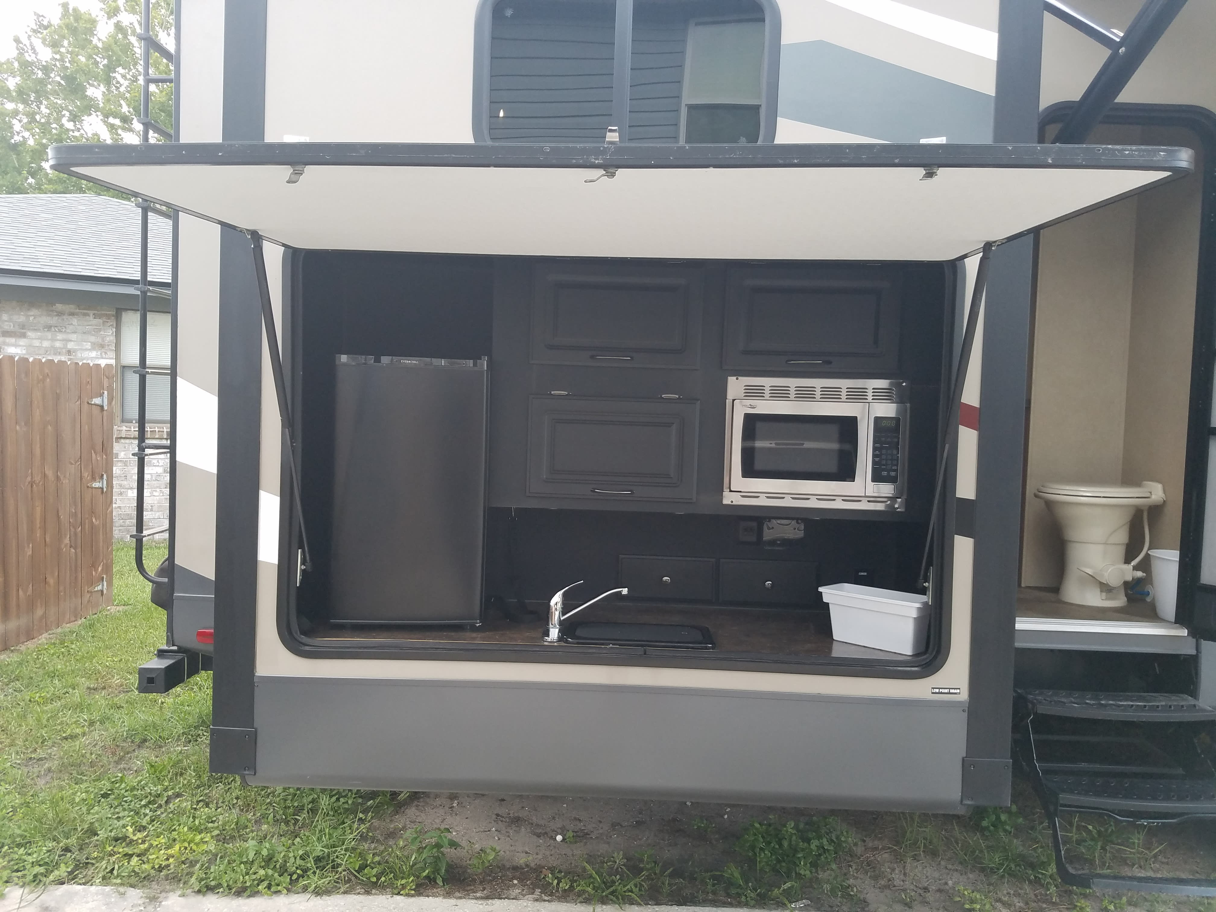 Out door kitchen with fridge, microwave, sink and propane grill. Forest River Sandpiper 2016