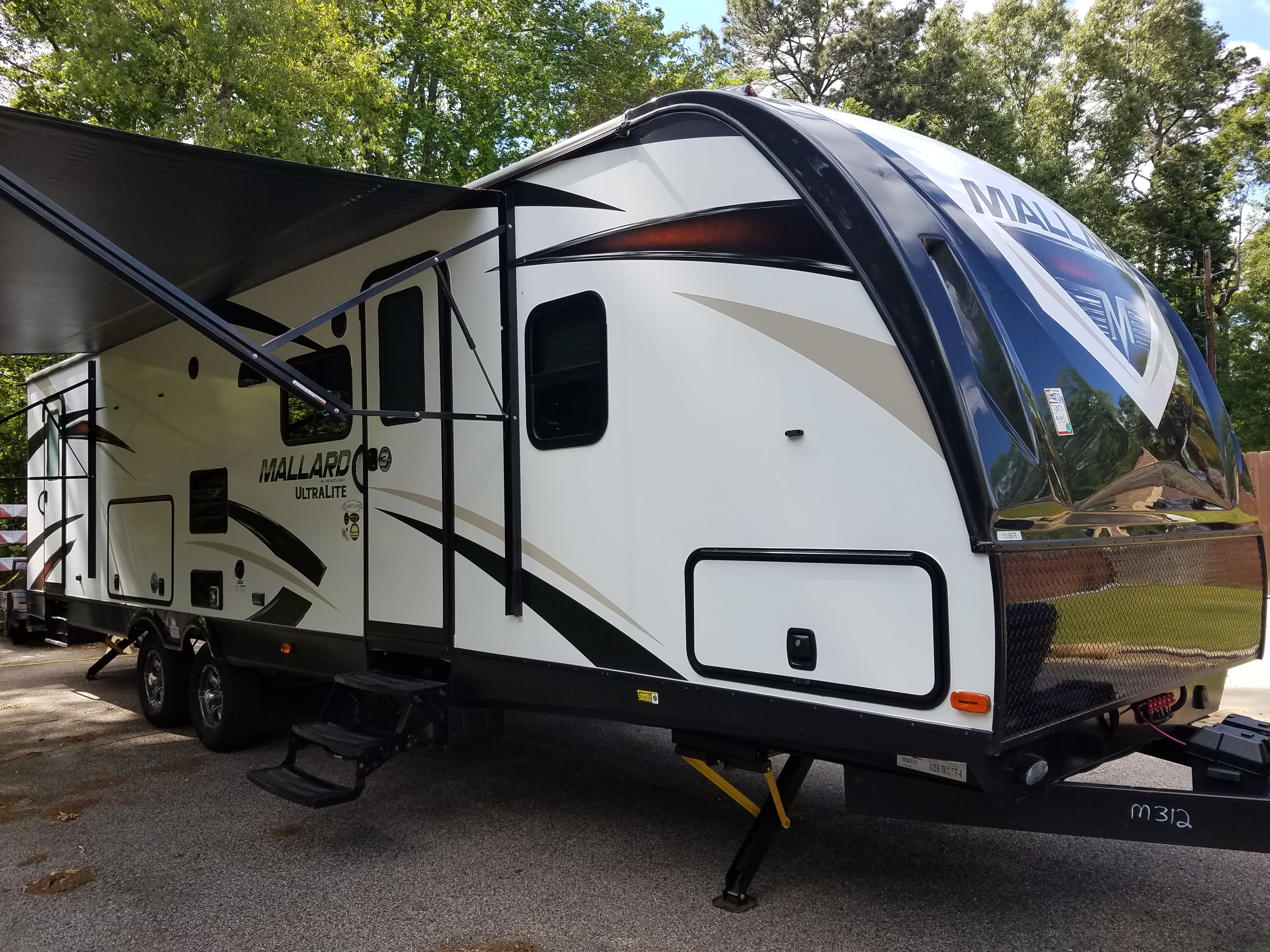 Front side view - Showing entrances and awning.  . Heartland Mallard 2018
