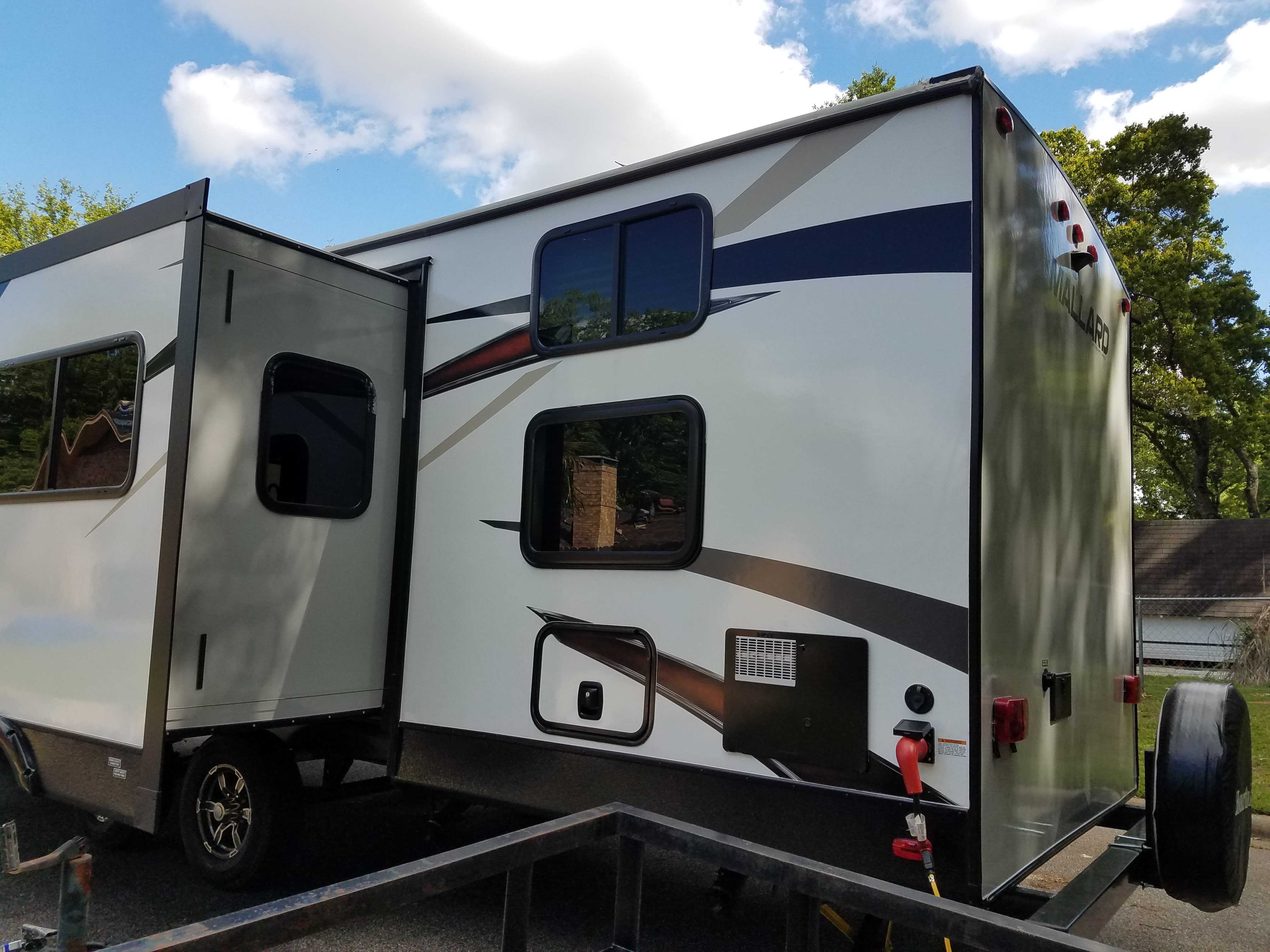 Slid-out side rear view with bunk windows, rear outdoor shower, and storage compartment.  . Heartland Mallard 2018
