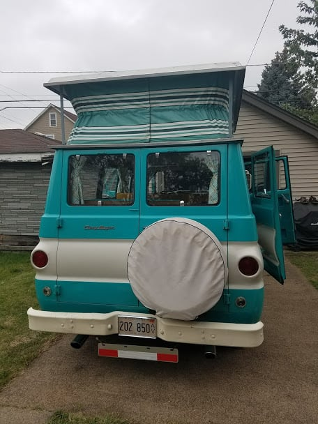 The rear of the CampWagon, showing spare tire and poptop up.. Dodge CampWagon 1967