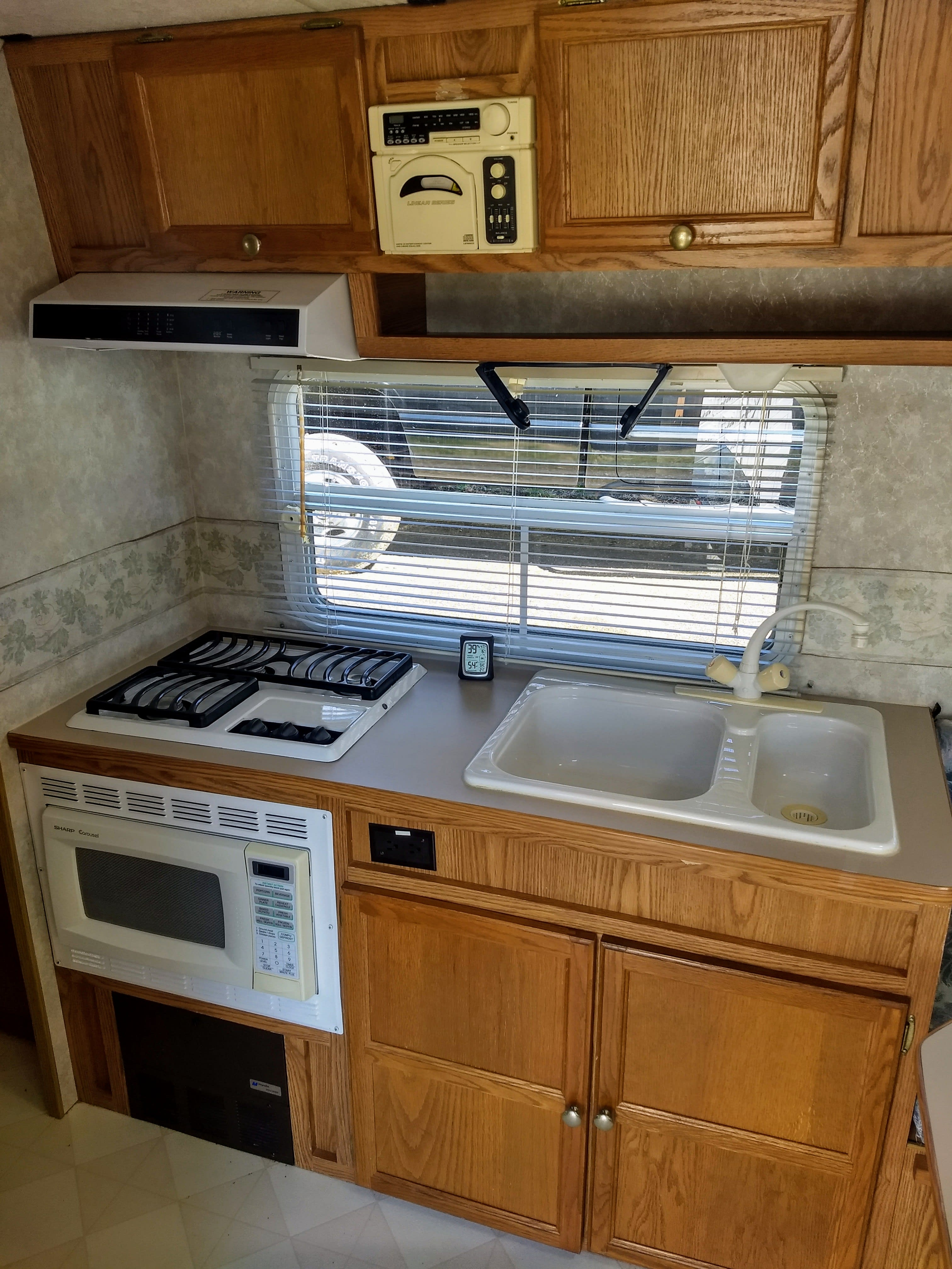 Kitchen includes sink, stove top and microwave. R-Vision Trail-Lite 2000