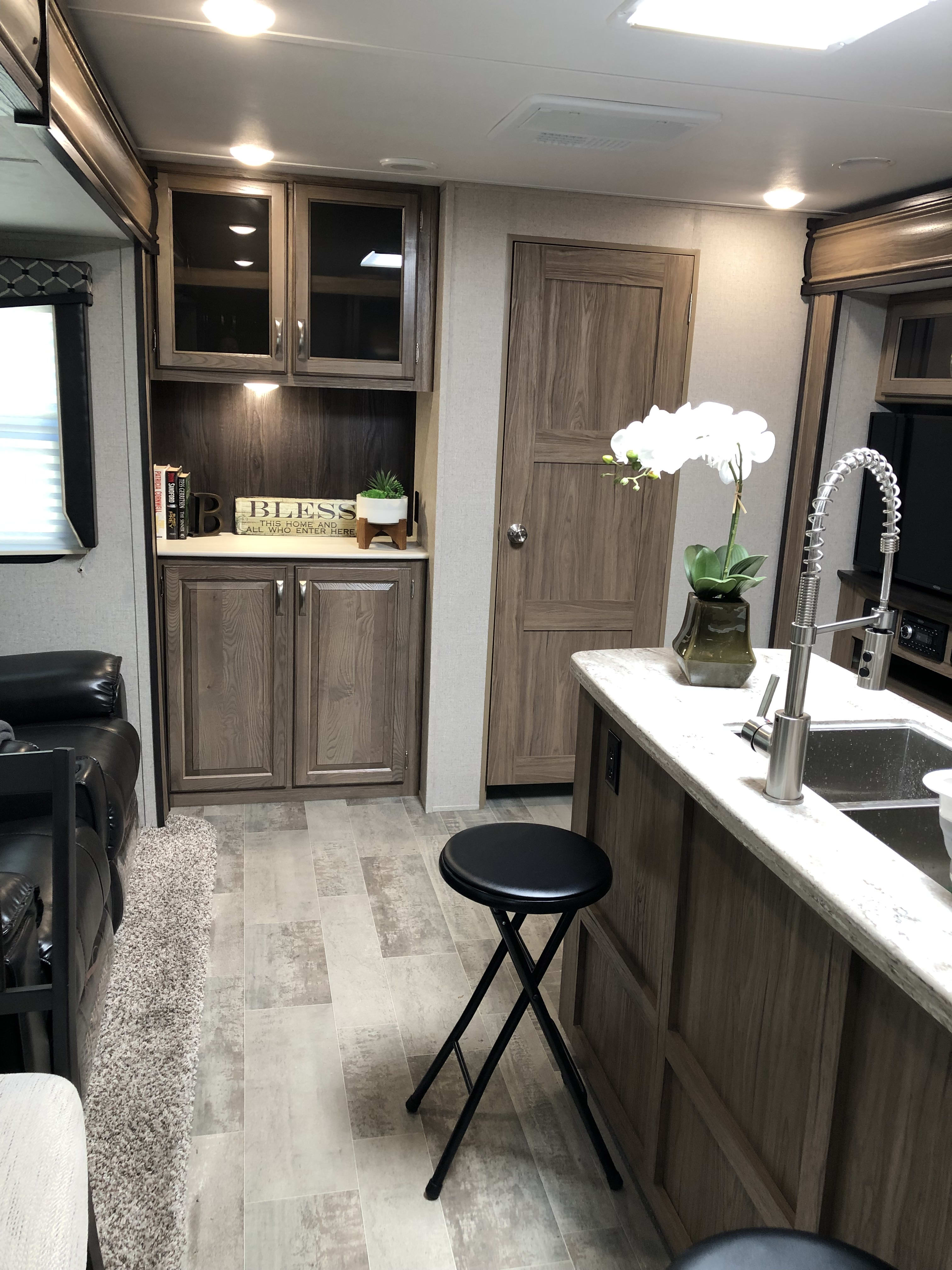 A view of the kitchen area through the RV toward the bunkhouse.  Our RV offers a spacious kitchen with island, roomy dining area with seating for 4 at the table and two at the island.. Dutchmen Atlas 2019