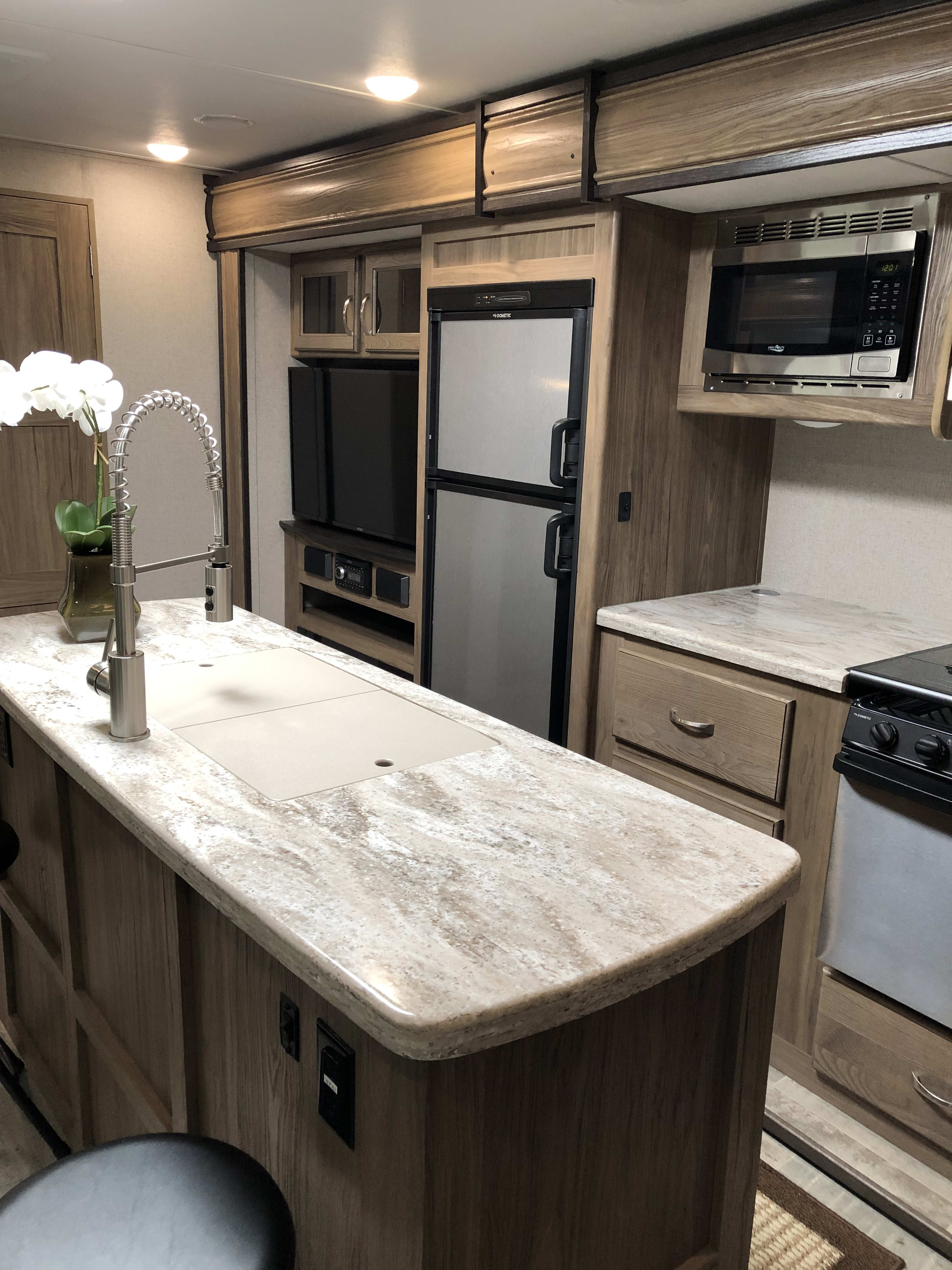 Note the large island and plenty of countertop for food prep.. Dutchmen Atlas 2019