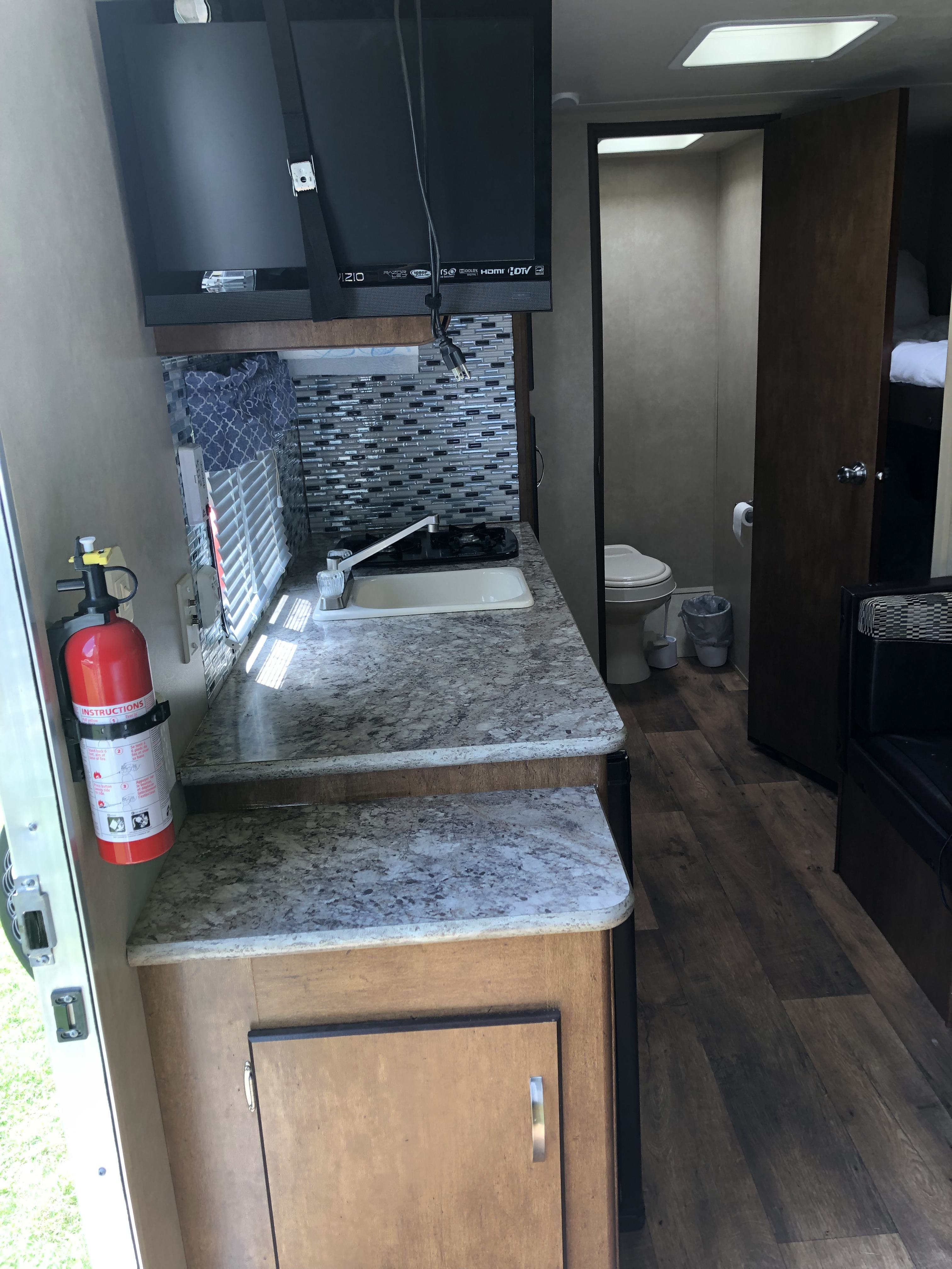 sink and stove top with microwave above counter and fridge below.. Forest River Salem Cruise Lite 2016