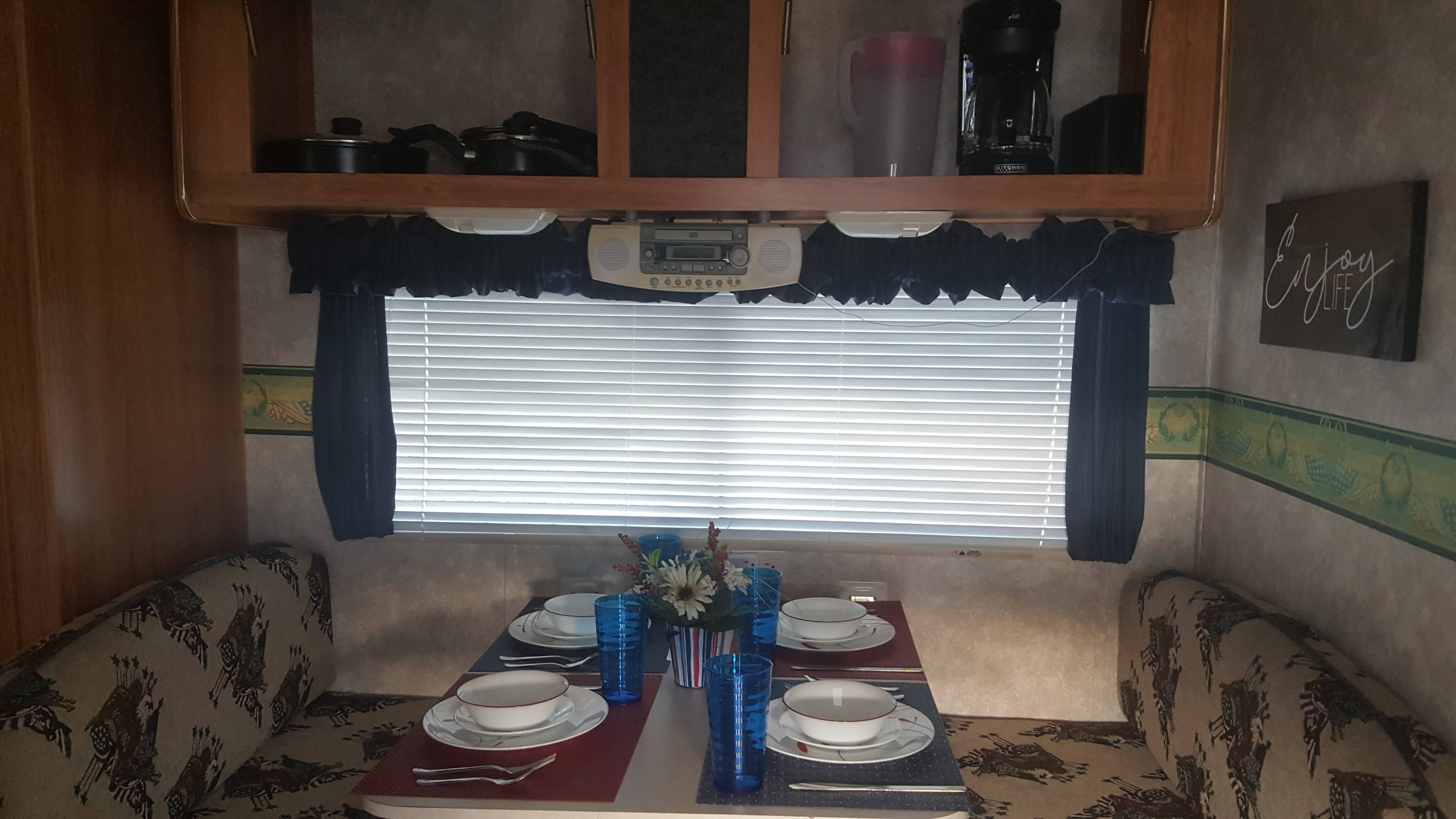 Dinning Table for four people. Pots and pans top left, Coffey pot Toaster and Pitcher top Right. Coachmen Spirit Of America 2003