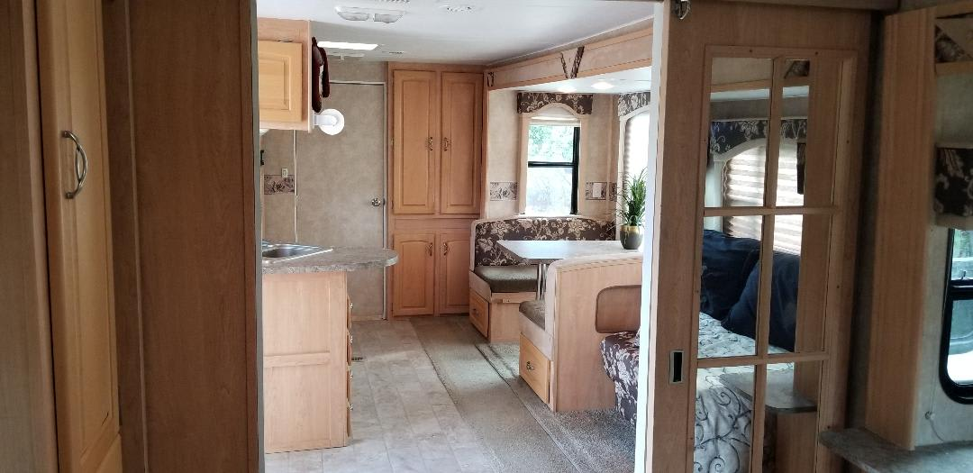 Living and kitchen area sliding mirrored doors from bedroom. Thor Motor Coach Jazz 2008
