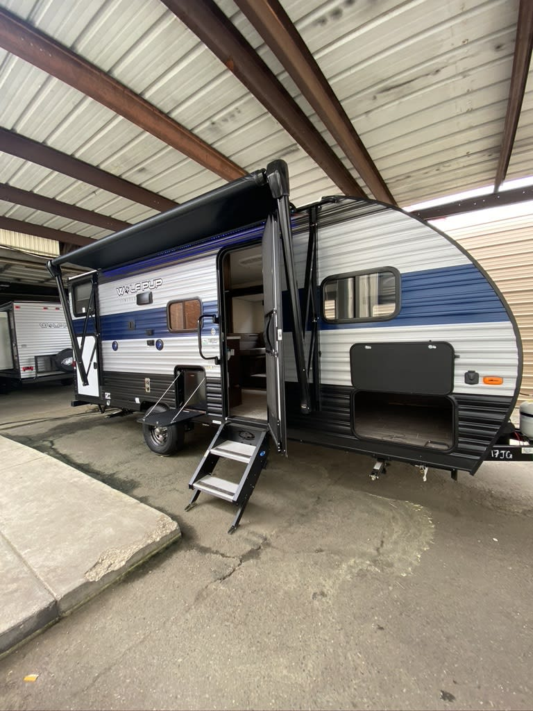 Side View showing Awning/Outdoor TV mount/Sturdy Step/Outdoor Fridge/Front Storage/Rear Bunk Storage Access. . Forest River Cherokee Wolf Pup 2021