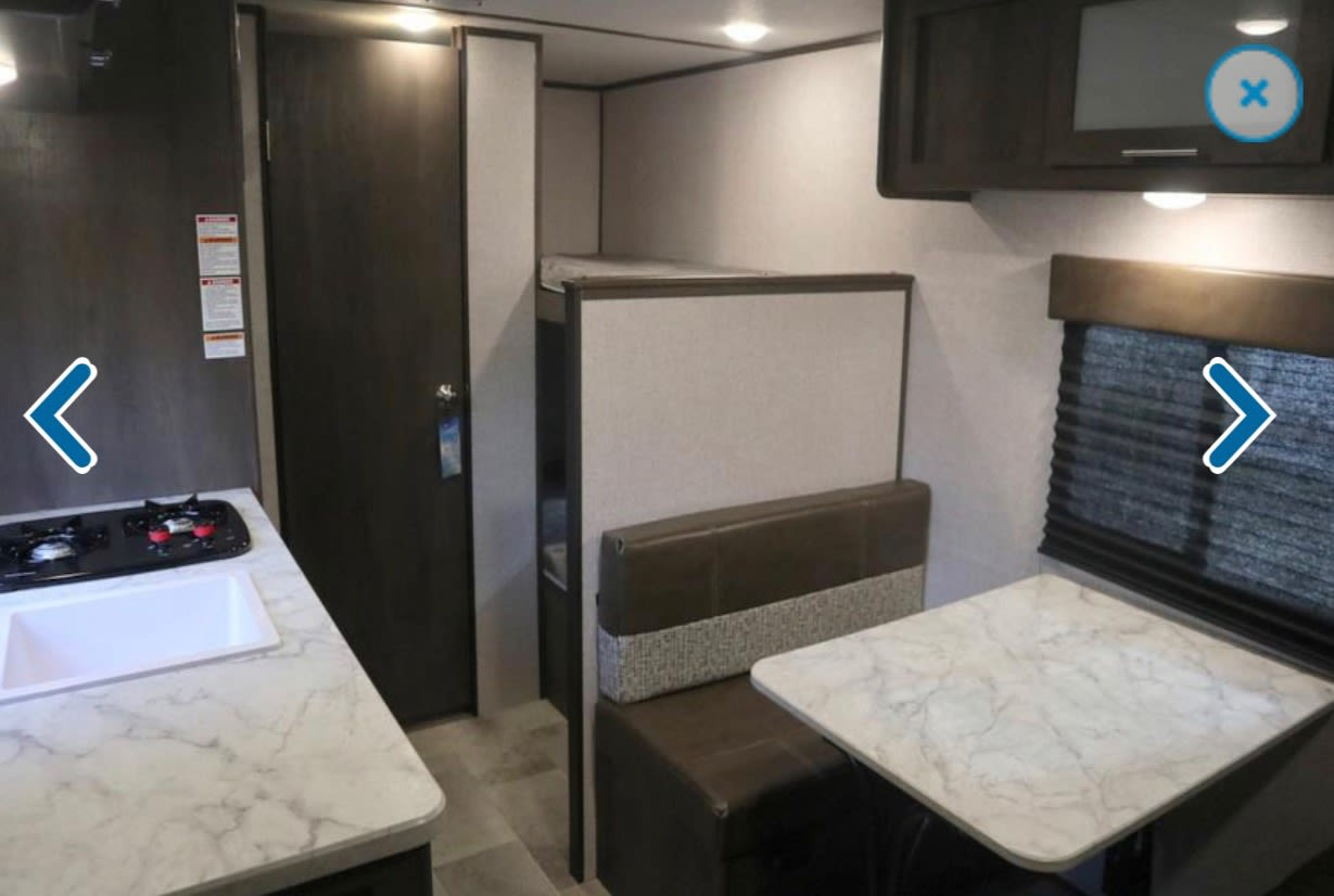 Interior table, kitchen, door to bathroom and bunks in back right. Coleman Other 2021