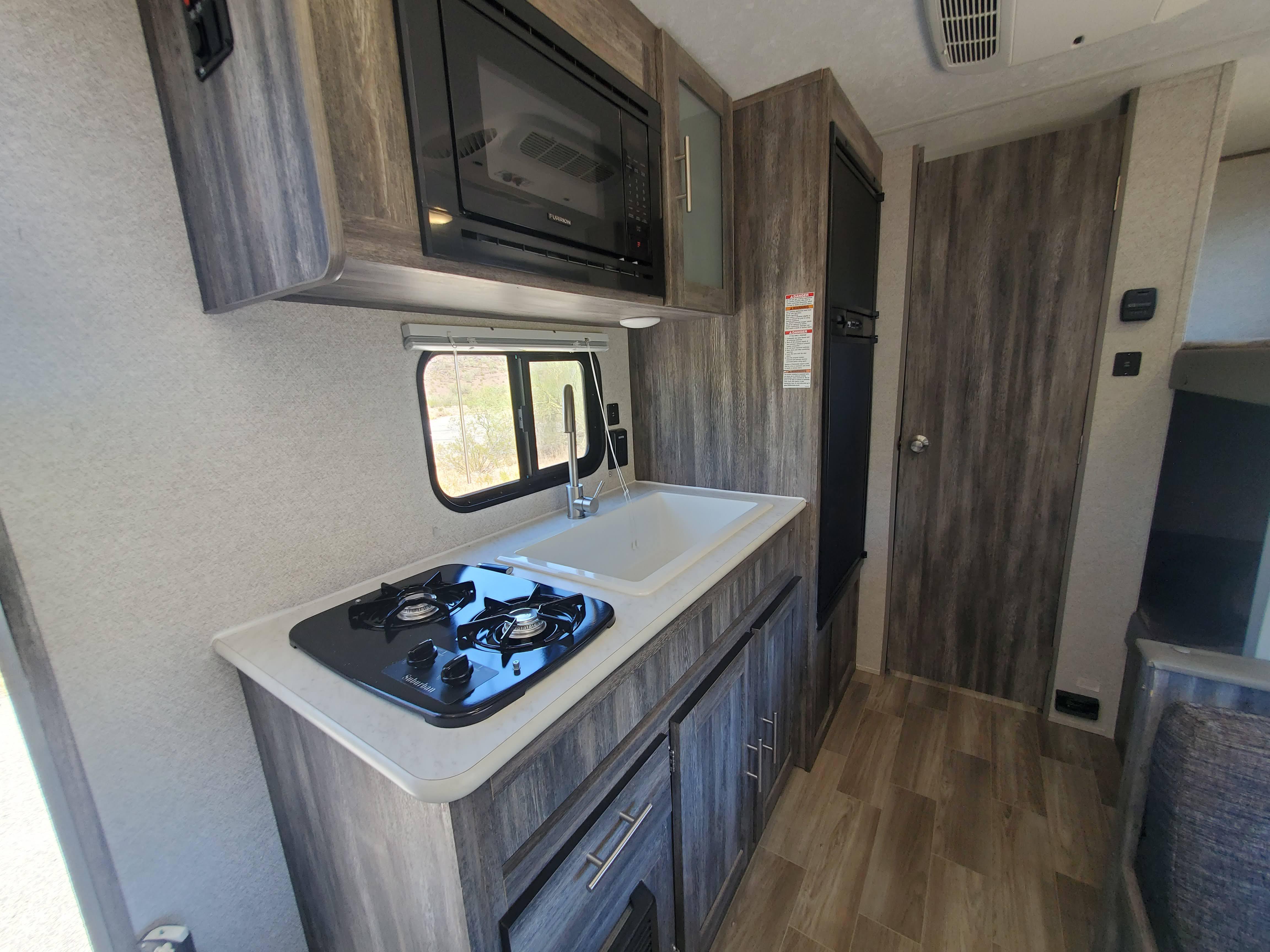 Kitchen with a 2 burner stove, large sink, microwave, and large fridge/freezer.. Forest River Salem 2019