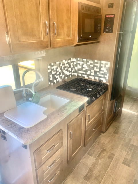 Kitchen area Includes double sided sink, water filter, stove top and microwave. Winnebago Outlook 2019