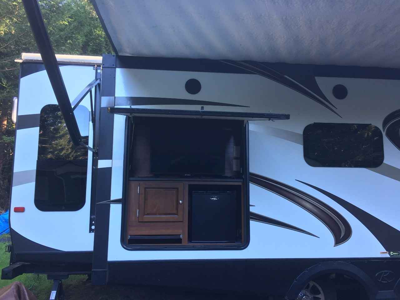 Outdoor entertainment compartment with mini refrigerator and TV.. Keystone Premier Ultra Lite 2015