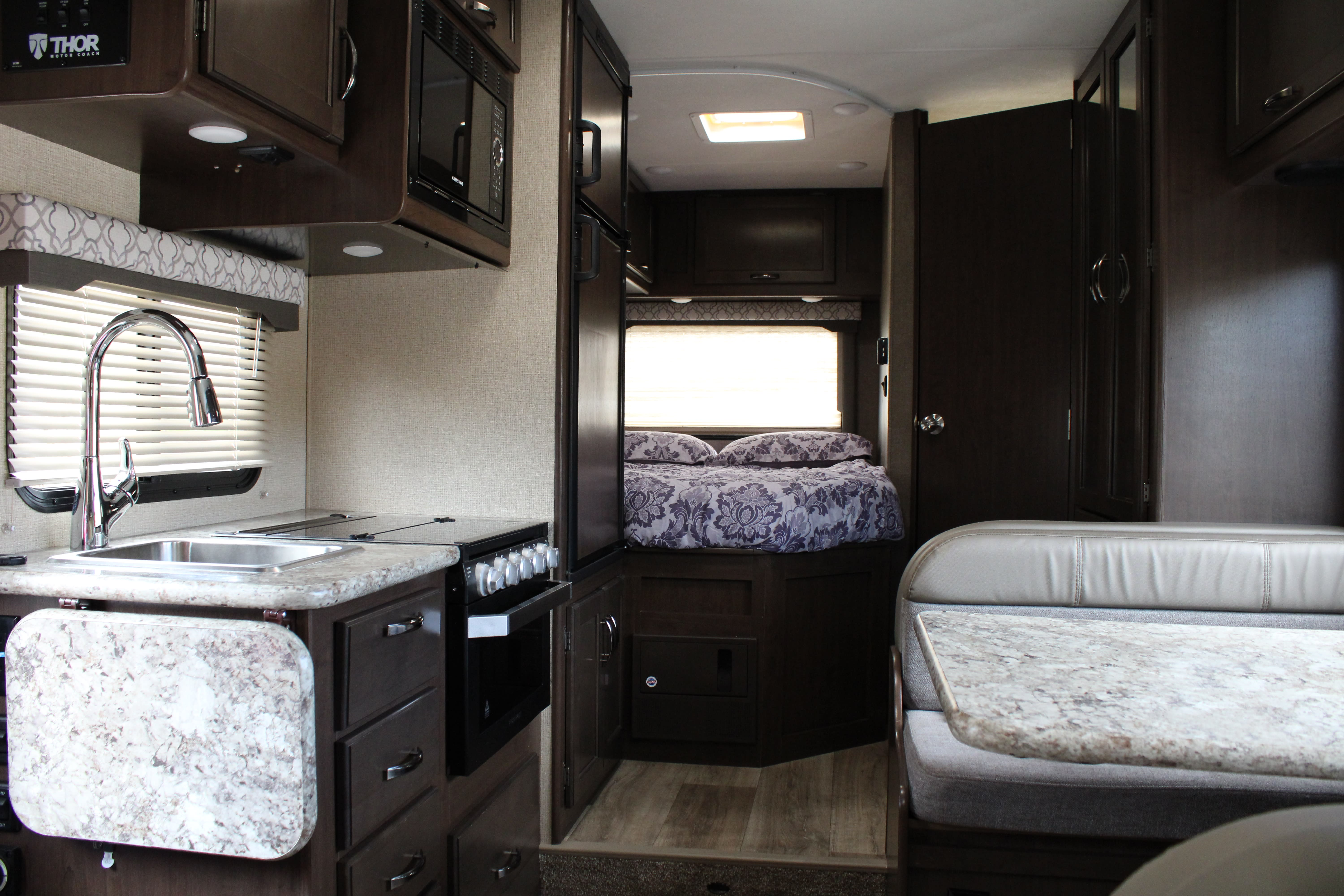 Interior living space; dinnette,  kitchen, queen-sized bed, and bathroom.. Thor Motor Coach Freedom Elite 2019