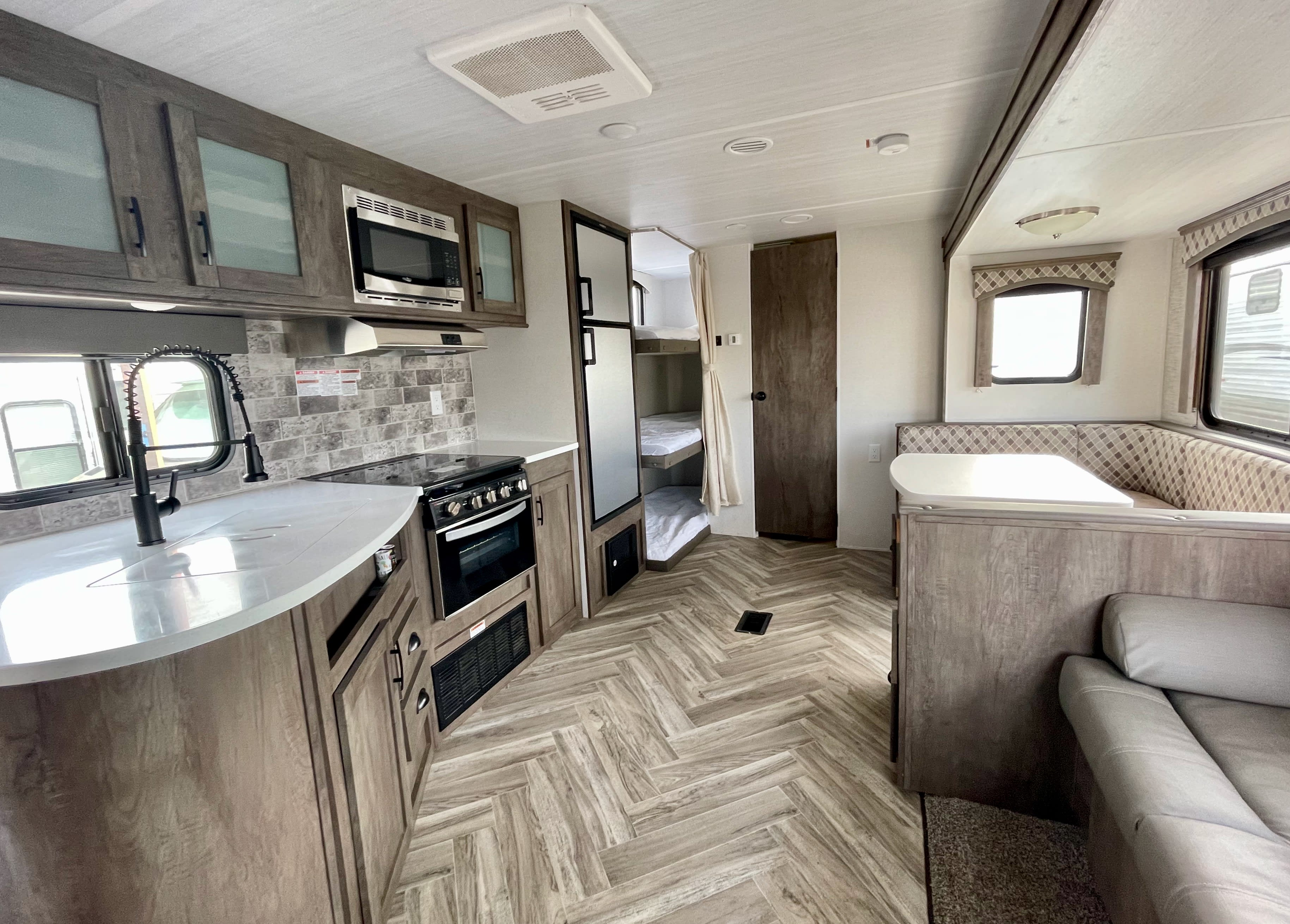 View of sofa, dinette, rear bunks and kitchen. Forest River Evo T2550 2018