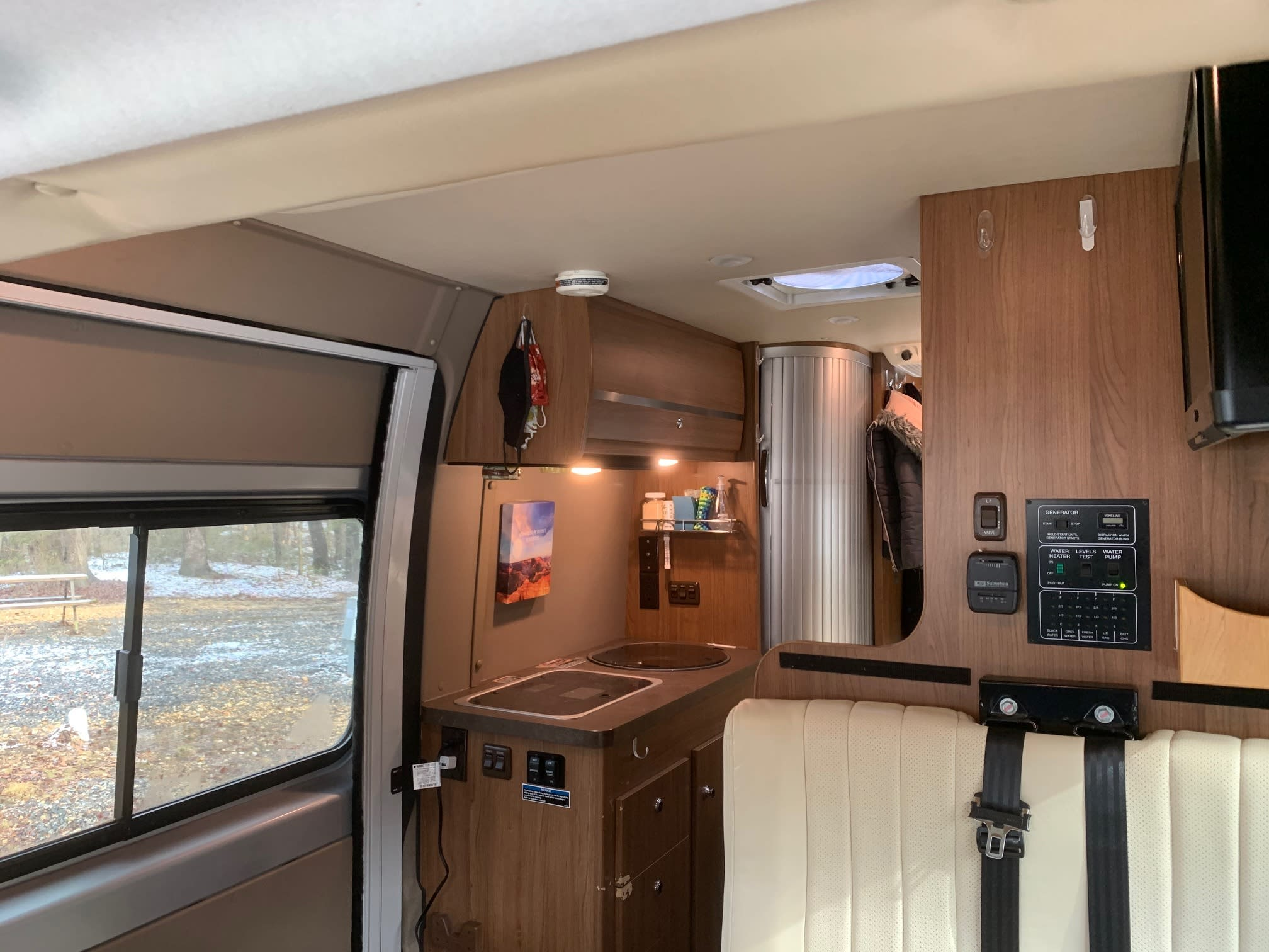 View of the stove and sink, and sliding door -which has a full-coverage accordion screen door (it's in the closed position in this photo). Winnebago Travato 2015