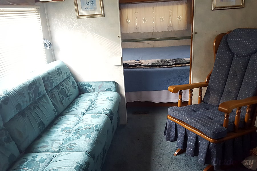 1994 Coachmen Catalina Zelienople, PA Couch, rocking chair, bedroom with sliding doors.