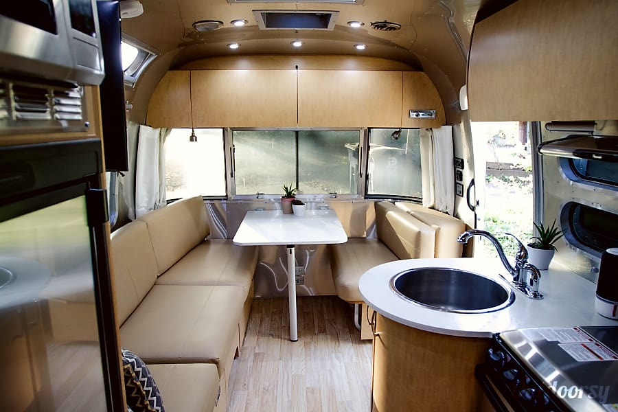 2017 Airstream Flying Cloud Dallas, TX Spacious living area with dining table sofa and television.
