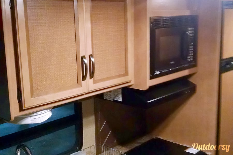 2015 Thor Motor Coach Axis Paris, IL Kitchen area with microwave, 3 burner stove, and oven.