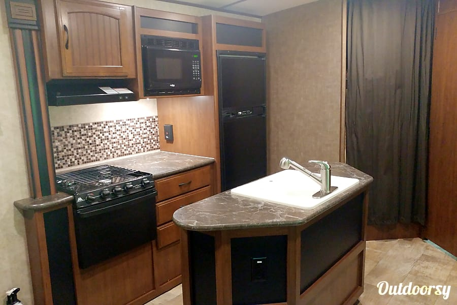 2016 Jayco Whitehawk 25BHS Cocoa, FL A modest cozy kitchen with a stove, oven, microwave, fridge, and freezer.  Not shown are the toaster and coffee pot, which are included.