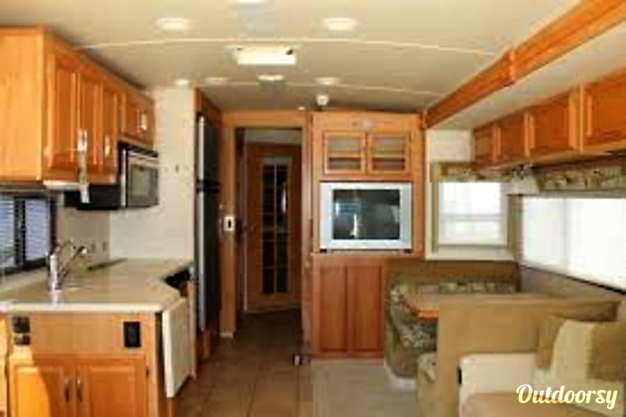 2007 Winnebago Adventurer Phoenix, Arizona Kitchen, dining room, TV and entrance to bath and bedroom.