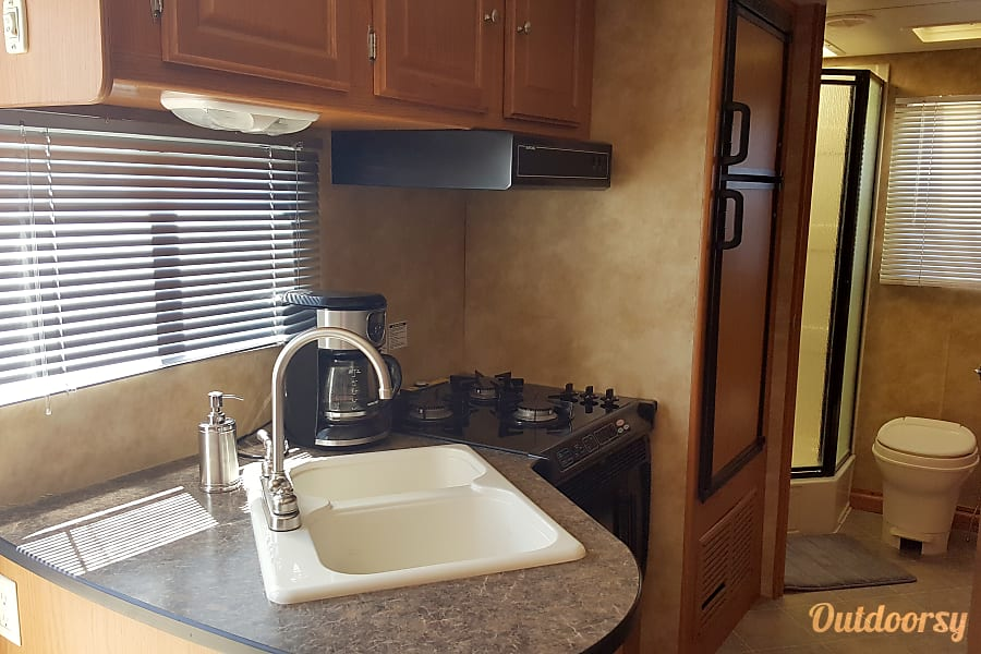 Rent North Trail 21FBS With Slide Out No Mileage Charge Las Vegas, NV Double sink, 3 burner stove, microwave and fridge freezer combo.