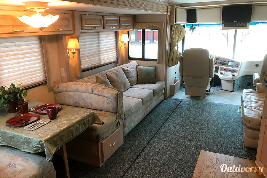 Fort Wilderness Express Newmarket, NH View of the living area from the galley. The large couch folds out to a bed and has seat belts for two.