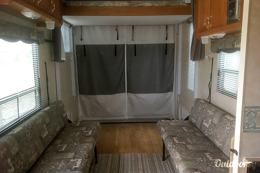 2006 Cherokee Wolfpack 30WP Columbia, IL Coach area with the twin couches that are used during the day for lounging.  The bed in the back is on a motorized track and comes down.  Two adults can sleep in this bed comfortably.