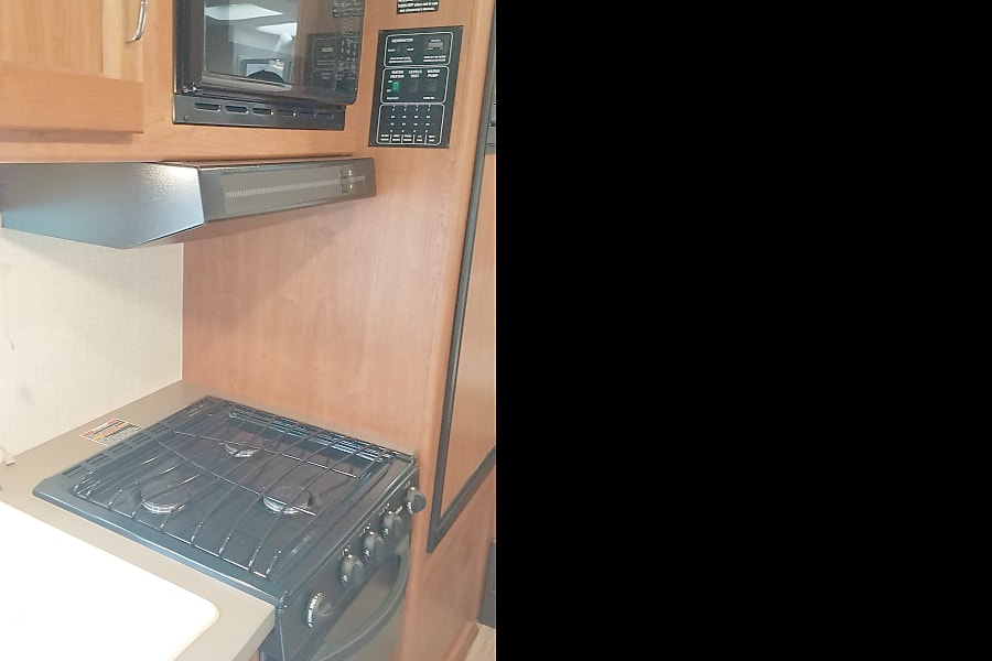 """""""The Country Cottage"""" Georgetown, TX Galley with oven, microwave and 3 burner stove."""