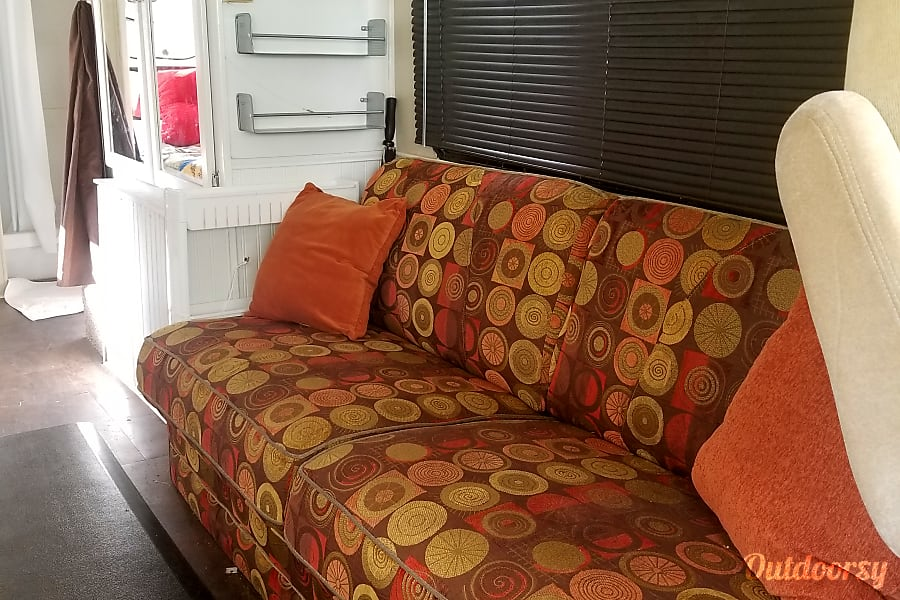 Restored Vintage Winnie Yuba City, CA Sleeper couch, can sleep two people comfortably. There is a slide out shelf between it and the wardrobe.