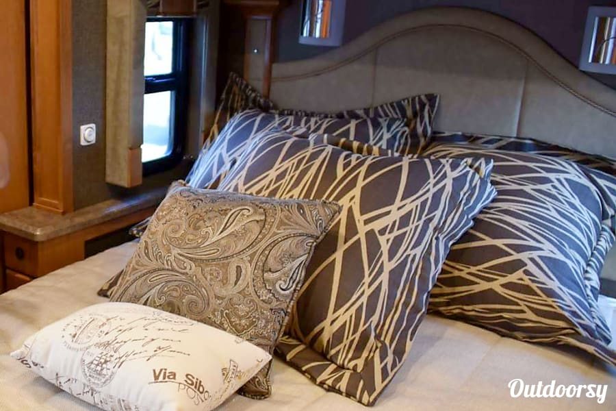 Magic Bus Lake Forest Park, WA The RV sleeps five. This queen bed in the bedroom, two on the hideaway couch bed and a hidden bed that lowers from the front of the coach.