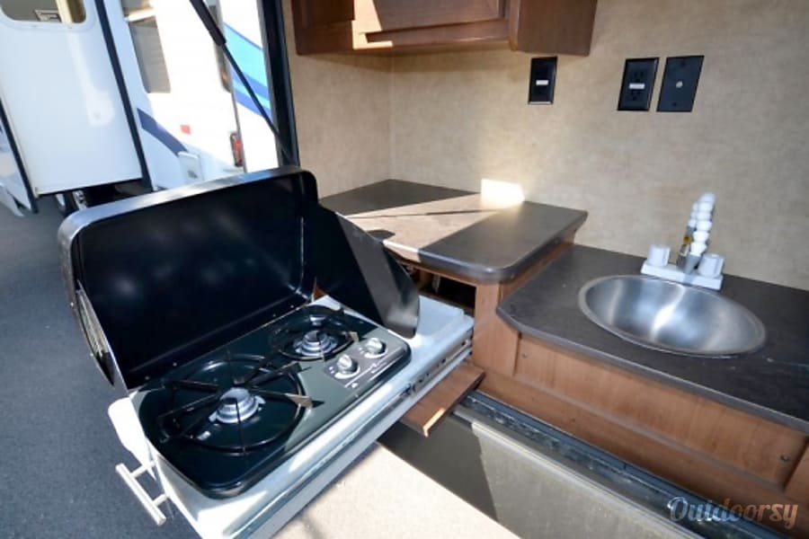 Family Friendly Value 2014 Aerolite Travel Trailer Pearland, Texas Outdoor kitchen with propane stove, sink and refrigerator keeps your indoor kitchen clean