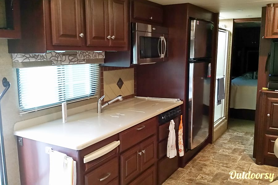 2013 Thor Motor Coach Palazzo Palm Bay, Florida Kitchen with Solid surface counters, Microwave/Convection & 18 Cubic foot Residential Refrigerator with icemaker