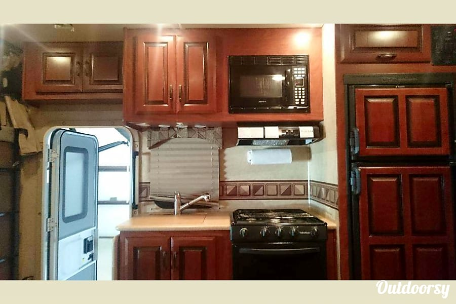 2013 Mercedes-Benz Sprinter Austin, Texas Kitchen with refrigerator, gas stove, oven, microwave and sink.