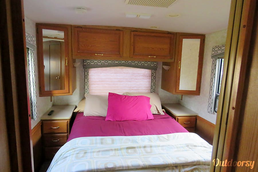 1999 Itasca Suncruiser Grove City, OH Queen bed with additional storage underneath.