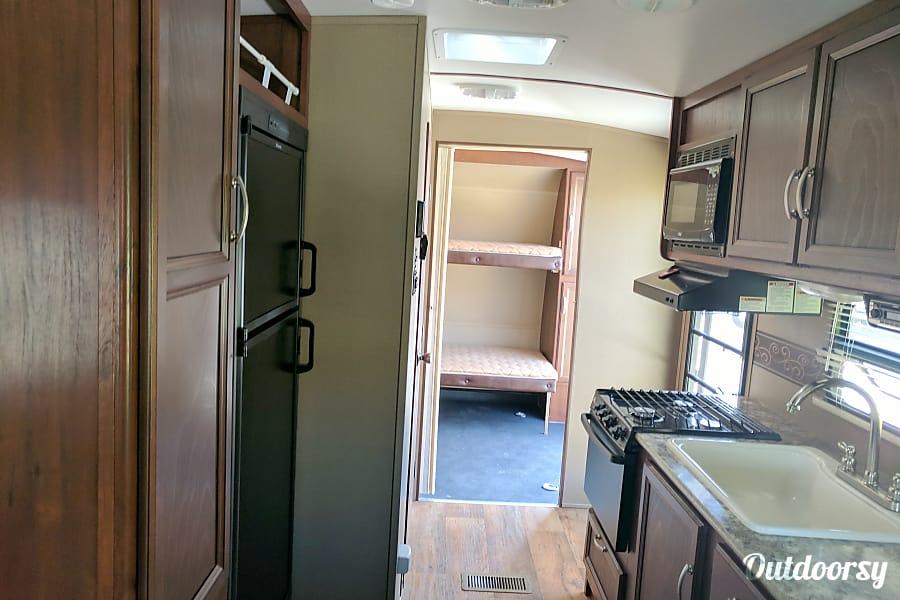2016 Keystone Outback Terrain Timnath, Colorado 6cu fridge, pantry, micro and view of bunks.
