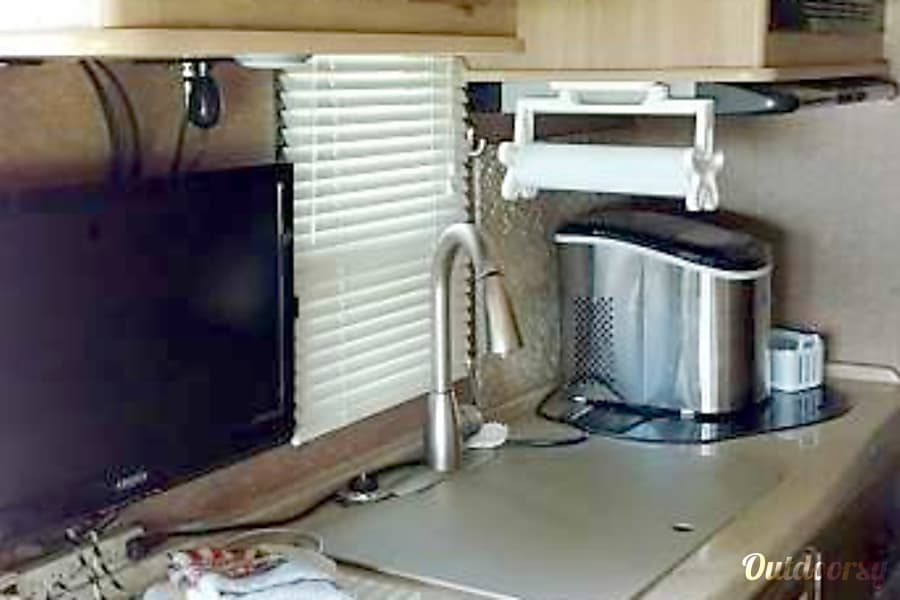 2015 Coachmen Prism 24G Albany, Georgia Kitchen area with double sinks, counter top, stove top, microwave oven, refrigerator