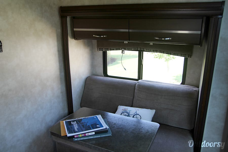2011 Itasca Navion Huntsville, AL Couch, with dinning table setup.  RV include a ottoman with additional storage