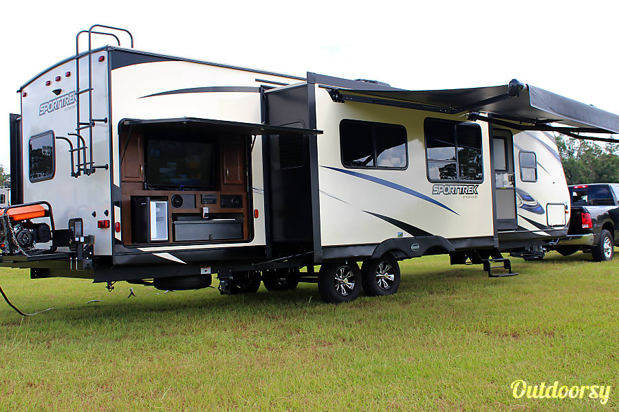 2018 Venture Rv Sporttrek Kissimmee, Florida Exterior view which shoes the outdoor kitchen/entertainment area. The outdoor kitchen area is equipped with a large TV, two burner stove, sink, refrigerator, and storage.