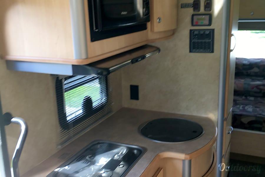 2008 Itasca Navion Idaho Falls, Idaho Kitchen with 2 gas burners, sink, microwave and overhead hood