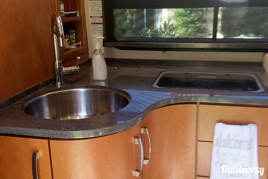 2016 Leisure Travel Unity Poway, California kitchen has a sink and stove shown here, but also a large refrigerator and microwave convection