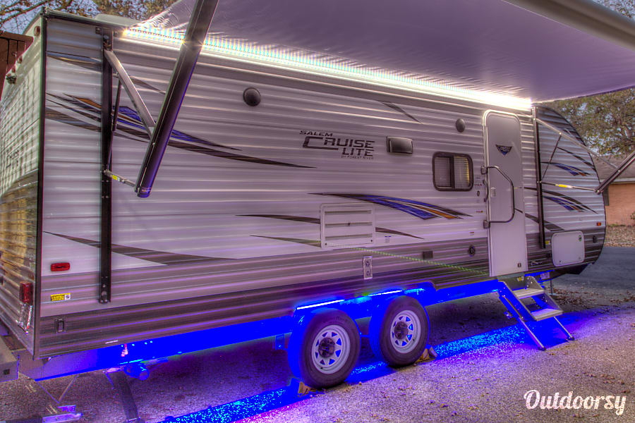 2018 Forest River Cruise Lite 230BHXL Corsicana, Texas Picture of exterior with blue LED underside and LED running lights on the powered awning for  easily extended and retracted with the simple push of a button, affording you complete control over your shade. powered stabilizers and hitch jack and are all remote controlled. Easy set-up at campsite. RV also has outdoor speakers and Solar power ready.