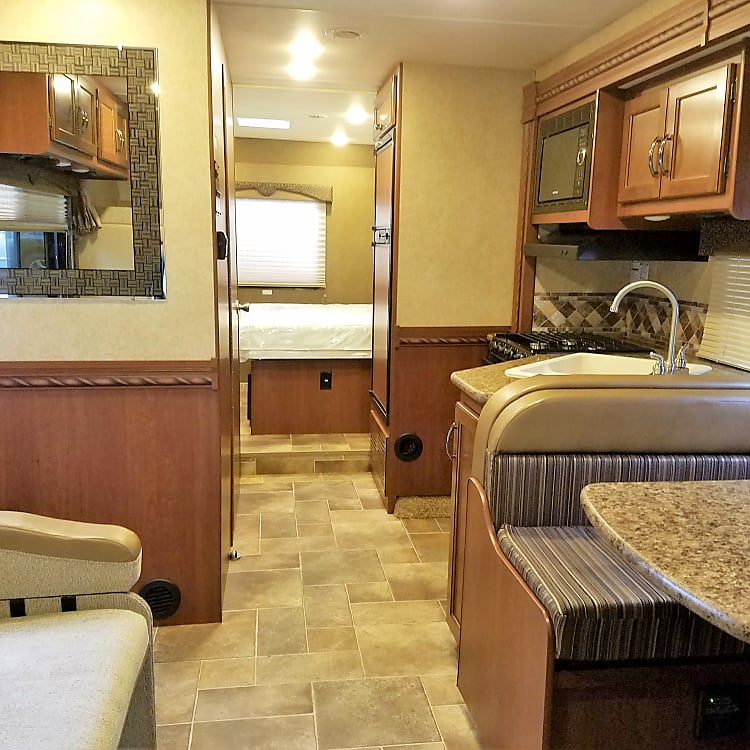 Interior of RV, looking towards the bedroom, with kitchen slide out extended. Very spacious, lots of seating.