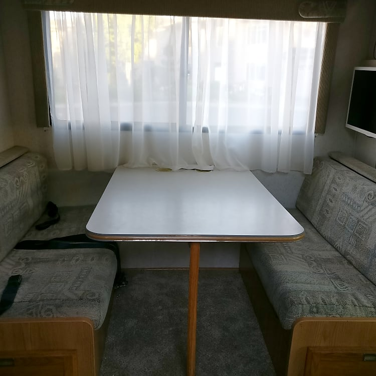 Dinette, sleeps two people when folded down. TV - runs off inverter during driving or when off-grid.