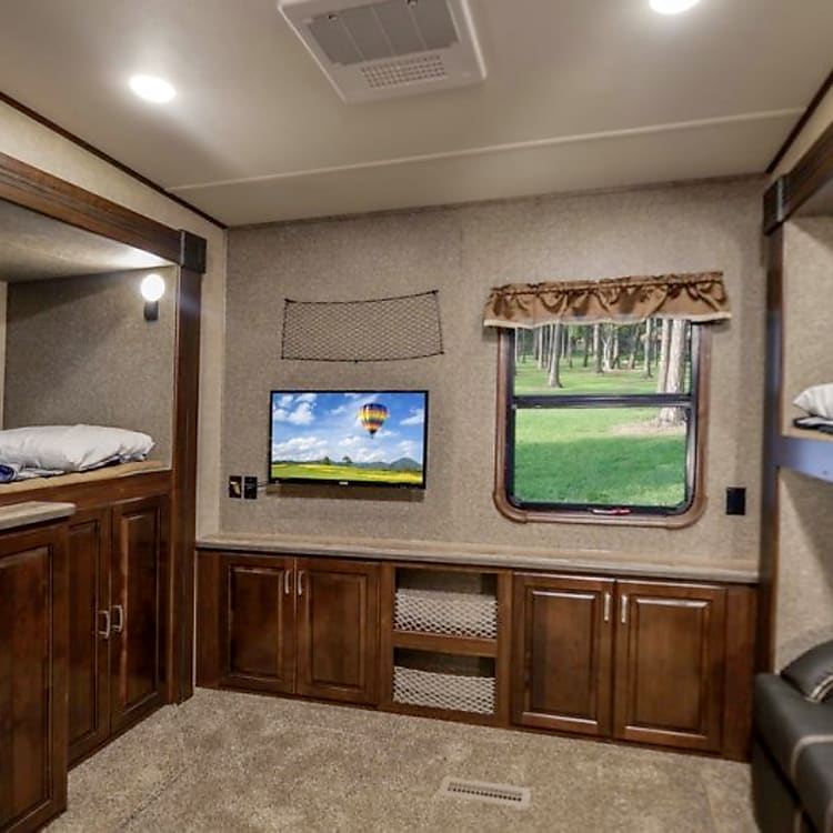 Spacious bunk room with lots of storage, it's own tv, half bathroom, and couch (that also folds out into a double bed).