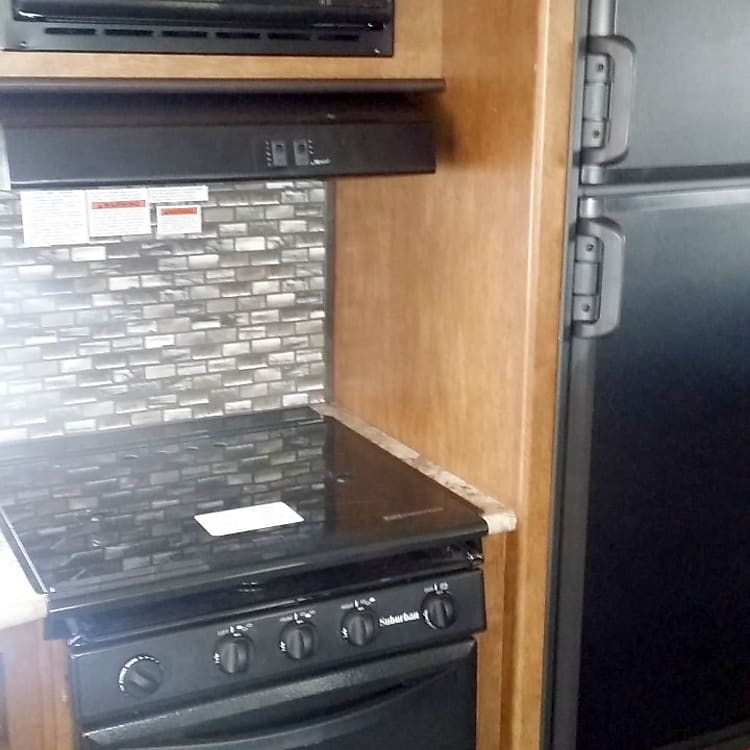 Microwave, stove top and oven in kitchen.