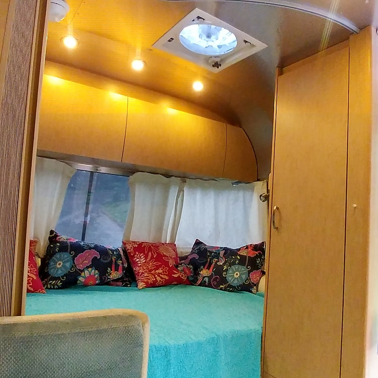 Close to full-size mattress. The overhead compartments and closet have plenty of room for two people to store clothes. The window by the bed opens up for fresh air.